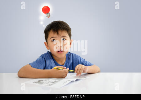 The boy is looking up,  While sitting on some writing on the notebook. - Stock Photo
