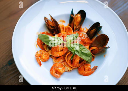 Tasty pasta with shrimps and mussels standing on the table - Stock Photo