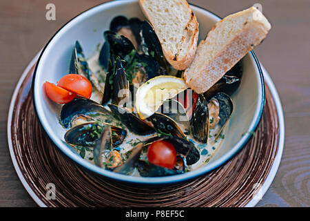 Mussels dish with some bread and little tomatoes - Stock Photo