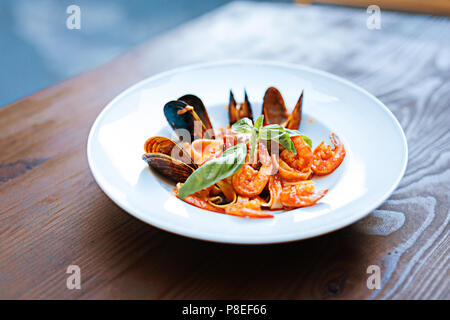 Close up of delicious pasta with some seafood in tomato sauce - Stock Photo