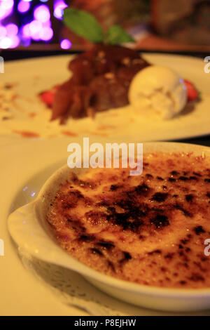 French Cuisine: Crème brûlée (in focus) and Tarte Tatin with Vanilla Ice Cream (out of focus) - Annecy, Haute Savoie, France - Stock Photo