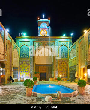 The scenic square in front of Ganjali Khan Mosque with small fountain and plants in pots, Kerman, Iran. - Stock Photo
