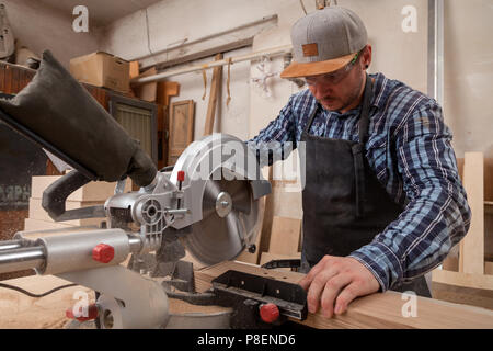 carpenter work with circular saw for cutting boards, the man sawed bars, construction and home renovation, repair and construction tool - Stock Photo