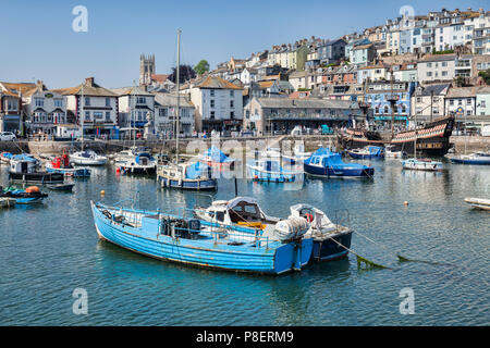 23 May 2018: Brixham, Devon, UK - The harbour with the replica Golden Hind on a fine spring day with clear blue sky. - Stock Photo