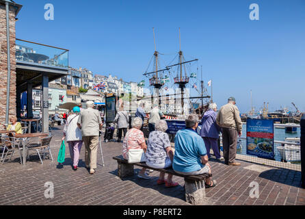 23 May 2018: Brixham, Devon, UK - Senior citizens relaxing on the seafront at Brixham Harbour, with the replica Golden Hind sailing ship. - Stock Photo