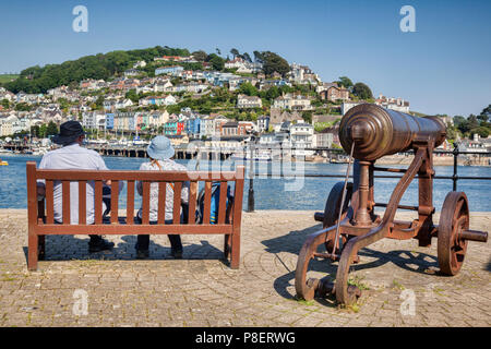 23 May 2018: Dartmouth, Devon, UK - Couple sitting on a bench beside an old cannon, looking out over the River Dart. - Stock Photo