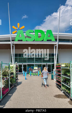 28 May 2018: Newton Abbot, Devon, UK - Asda supermarket entrance, with a woman pushing a trolley towards it. - Stock Photo