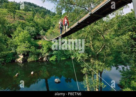 Woman and man crossing suspension bridge over river - Stock Photo