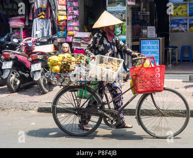 Daily life, a female street vendor selling fruit from her bicycle on the street in Ho Chi Minh City, Vietnam. - Stock Photo