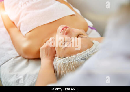 Pretty woman receiving facial massage - Stock Photo