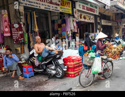 Daily life, a female street vendor selling fruit from her bicycle and a man resting on his motorbike on the street in Ho Chi Minh City, Vietnam. - Stock Photo