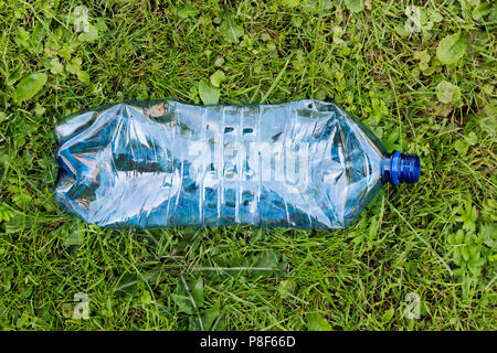 Crushed blue plastic bottle laying in grass. Pollution and environment concept - Stock Photo