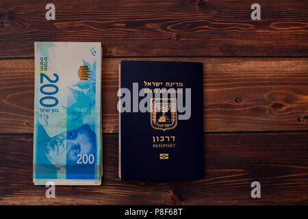 Fan of two hundred Israeli Shekel bills together with Israeli passport - Stock Photo