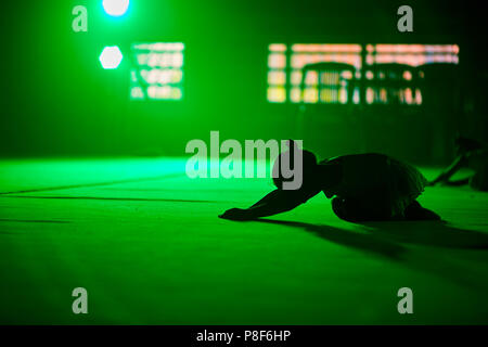 young girl athlete gymnast performs acrobatic elements in a green scenic light. - Stock Photo