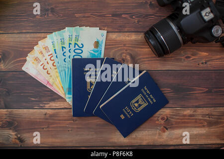 stack of Israeli money bills in the amount of 200 shekels and an Israeli passport on a wooden table - Stock Photo