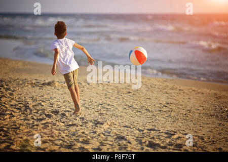 boy playing with ball on beach - Stock Photo