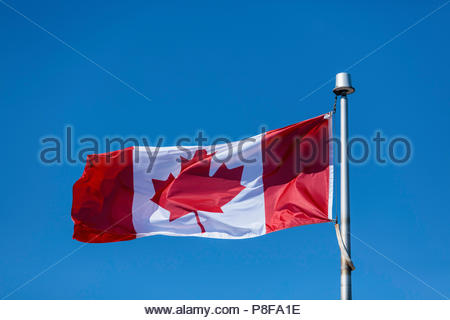 Canadian flag waving in the breeze against a clear blue sky in Canada - Stock Photo