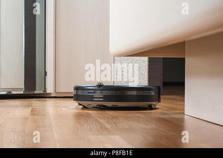 black Robot vacuum cleaner runs under bed on laminate floor in bedroom. modern smart cleaning technology housekeeping. - Stock Photo