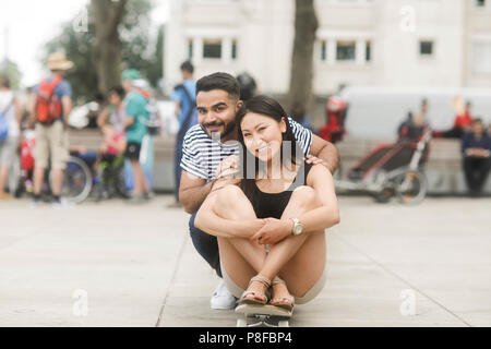 Smiling couple sitting on a skateboard in a city square - Stock Photo