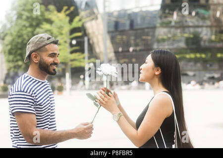 Man standing in city square giving his girlfriend a white rose - Stock Photo