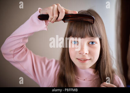 little girl with freckles and blue eyes combing her hair - Stock Photo