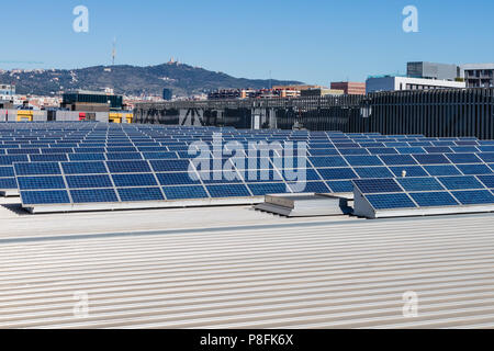 Field Photovoltaic solar production panels on a building roof - Stock Photo