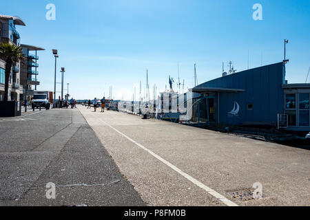 People walking along Poole Quay on a lovely warm summers morning, Poole, Dorset, United Kingdom - Stock Photo