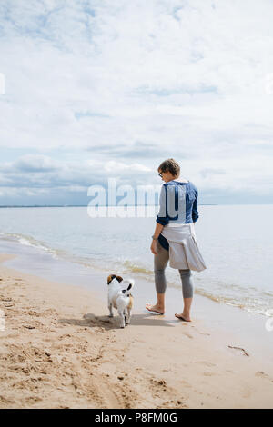 Woman walking with her dog on the sandy beach. Rear view. - Stock Photo