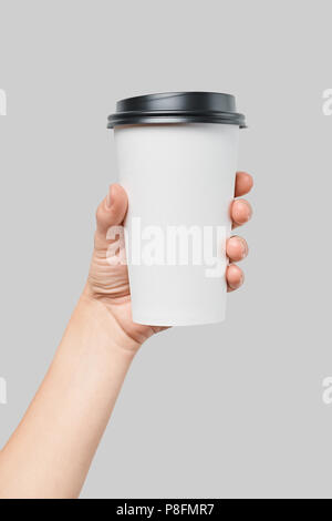 Mockup of women's hand holding white paper large size cup with black cover