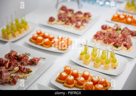 the buffet at the reception. Assortment of canapes. Banquet service. catering food, snacks with salmon - Stock Photo