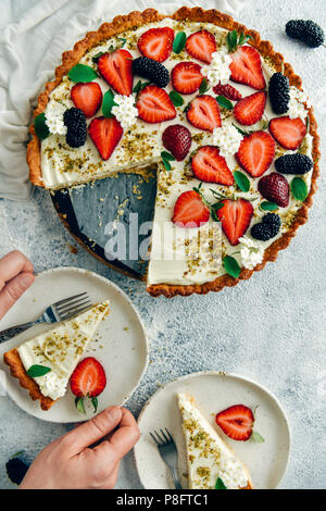A woman serving a slice of strawberry cheese pie on a white plate. Another slice and the rest of the pie accompany with lots of strawberries and mulbe - Stock Photo