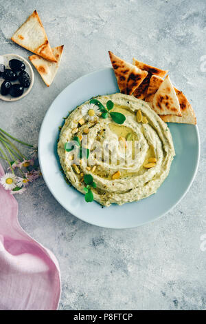 Creamy white bean hummus topped with herbs, olive oil and pistachios served in a light blue bowl with pita chips on the side. Black olives, spring flo - Stock Photo