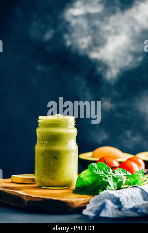 Avocado dressing in a glass jar photographed on a wooden board from front view. Arugula leaves, tomatoes, avocado with its pit accompany. - Stock Photo
