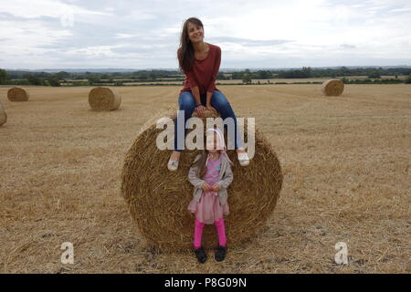 Beautiful mother and daughter in straw field in summer at harvest time - Stock Photo