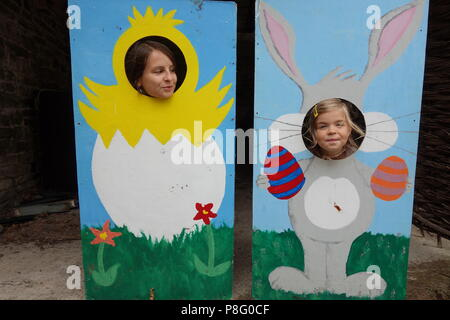 Mother and daughter having fun fairground beach attraction face-in-hole board - Stock Photo