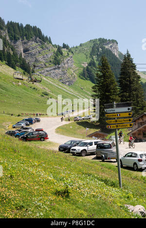 Mountain Bikers Taking Part in a Long Distance Time Trial at Les Lindarets in the French Alps along with Signpost near Montriond Haute-Savoie France - Stock Photo