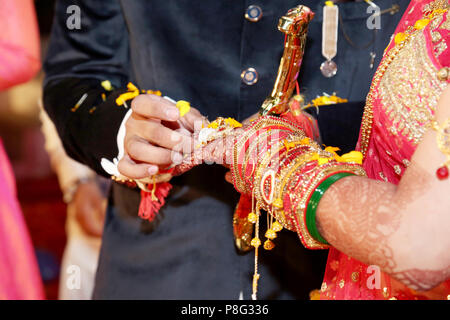 Indian groom putting ring on indian bride - Stock Photo