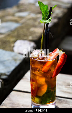 A Pimm's in a glass on a wooden table - a mint sprig like a tree - Stock Photo