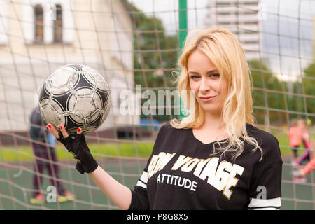 Beautiful blonde with a ball at the football goal. Football field at the gate close-up. - Stock Photo