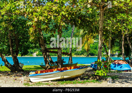 Boats lying in the sand under trees at a beach on Guadeloupe - Stock Photo