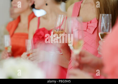 Bridesmaids in coral dresses drinking champagne - Stock Photo