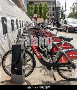Transport for London's Santander cycles (fka 'Boris bikes') self-hire bicycles at Aldgate docking station, in the City of London. Map and pedestrians - Stock Photo