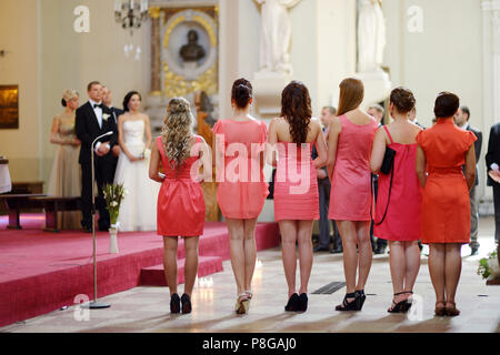 Row of bridesmaids in coral dresses at wedding ceremony - Stock Photo