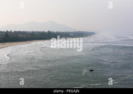 Lone fisherman braves the breaking waves in a canoe in Lăng Cô Bay (Cửa Biển Lăng Cô) Phú Lộc, Viet Nam - Stock Photo