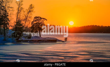 A tourist couple walks romantically in Lapland on a lake ice on a sunset. Atmospheric winter outdoor view. - Stock Photo