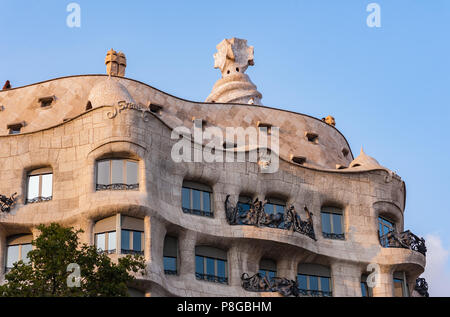 Waves and sculptural building details of La Pedrera, Casa Mila in Barcelona, Spain. Ornate architecture, view from below at sunset, vibrant colours. - Stock Photo