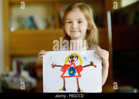 Little preschholer girl displaying her picture proudly - Stock Photo