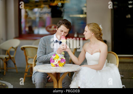 Bride and groom having an ice cream in outdoor cafe - Stock Photo