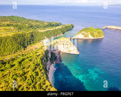 Indonesia. Rocky tropical coast of Penida Island and two small beaches, ocean and sunny weather. Aerial view - Stock Photo