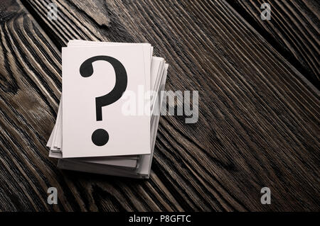 Stack of question mark cards on the wooden table with copy space - Stock Photo